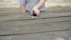 The old man with wrinkles uses the phone in the forest - stock footage