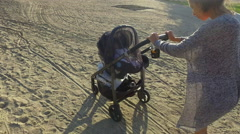 Mother pushes baby in stroller along beach - stock footage