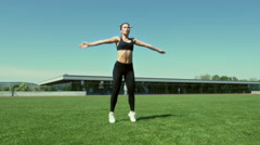 Young woman performing jumping jacks Stock Footage