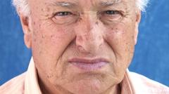 Worried old man looking in the camera: pensive retired elder: tilting footage Stock Footage
