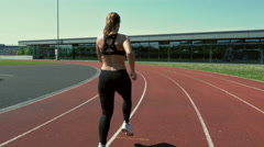 Young woman running around the track Stock Footage