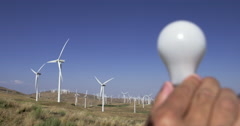 Wind turbines and electric light bulb illuminating 4K - stock footage