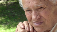 Old serene and thoughtful man: elder retired portrait in the park Stock Footage