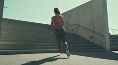 Young woman sprinting up the stairs Stock Footage