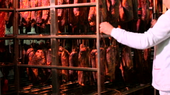 Worker transporting dried meat on a metal trolley in the food factory Stock Footage