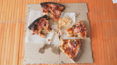 Hands taking pieces of pizza from a cardboard box Stock Footage