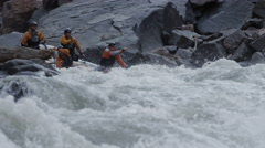 Guides whitewater rafting on raging rapids - stock footage
