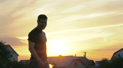 Handsome man pouring water over head on sunset. Slowly - stock footage