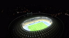 Soccer match on field at illuminated stadium, modern sports arena, aerial shot - stock footage