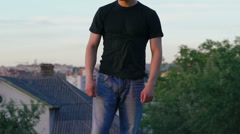 Young man undressing on the roof of building. Slow motion Stock Footage