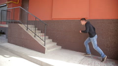 A free runner man vaults over a hand rail front flips down a set of stairs - stock footage