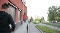 A free runner running near the modern building and doing parkour Stock Footage