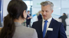 4K Friendly bank workers talking to customers & offering financial advice - stock footage