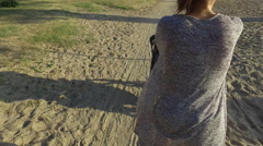 Young mom struggles to push stroller through sandy sidewalk Stock Footage