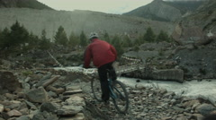Cyclists rush aside a raging river Stock Footage
