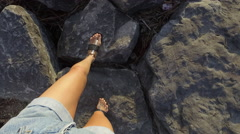 Woman walking on rocks unique fpv view of feet stepping tilt up to water Stock Footage