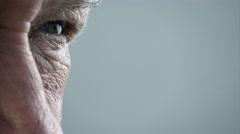 Elder man eye; old man's eye; pensive old man closeup portrait Stock Footage