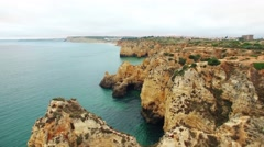 Cliffs in ocean near Ponte Piedade Lagos Portugal aerial view Stock Footage