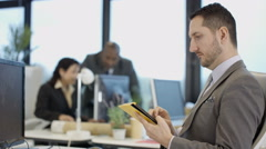 4K Portrait smiling businessman in city office with colleagues in background Stock Footage