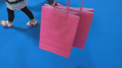 Pink shopping bags and women legs on blue background Stock Footage
