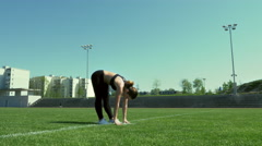 Young woman performs standing toe touches Stock Footage