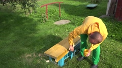 Amateur worker boy painting wood surface with brush in yellow color. Closeup. 4K Stock Footage
