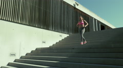 Young woman sprinting down the stairs Stock Footage