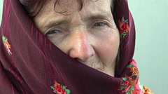 Pensive woman looking in camera and dressing headscarf: thoughtful old woman Stock Footage