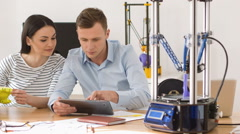 Pleasant colleagues using 3d printer - stock footage