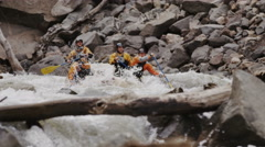 Whitewater Rafters Paddling Down Crazy Rapids With Large Splashes Stock Footage