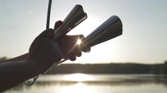Playing a musical instrument agogo on background sky at sunset - stock footage