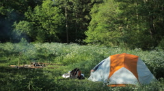 Man goes out in the morning Tents in the forest. Near the fire smokes. White man Stock Footage