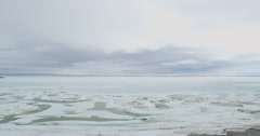 Wide scenic pan of frozen bay to sheer mountains on cloudy day - stock footage