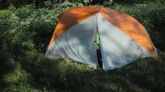The man opens the tent and starts to talk on the phone in the forest Stock Footage