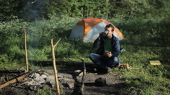 The man is drinking tea near the fire and taking pictures the forest and tent Stock Footage