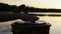 Playing a musical instrument jembe or atabaque on background sky at sunset Stock Footage