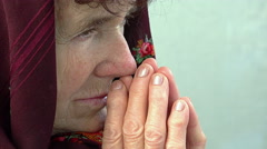 Faithful old woman praying, isolated portrait with scarf over head: seeking God Stock Footage