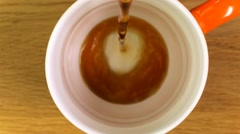 Top view of pouring black coffee into a mug against a wooden background Stock Footage