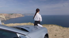 Relaxed business woman looking away leaning on her car at the sea shore Stock Footage