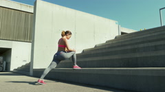 Young woman performing the Stationary Stair Lunge Stock Footage