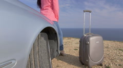 Relaxed woman with travel suitcase leaning on car bonnet looking out to sea Stock Footage