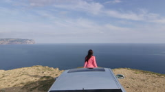 Rear view of young woman leaning on car bonnet looking out to sea jib crane shot Stock Footage