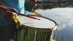 Playing a musical instrument repinique or drum on background sky at sunset Stock Footage