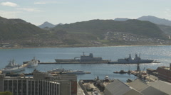 4k Naval Base & Ships On Dock Ocean Water & Mountains In Background Stock Footage