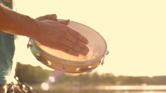 Musical instrument tambourine or pandeiro on a background of the sky at sunset Stock Footage