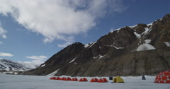 Clouds pass over mountain above line of expedition tents on sea ice Stock Footage