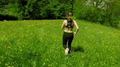 Young woman jogs down a hill Stock Footage