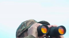 Hunter looks in binoculars Stock Footage