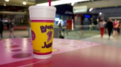 Motion of booster juice on table at food court area inside shopping mall - stock footage