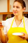 Mature woman holding cup of coffee in kitchen. Stock Photos